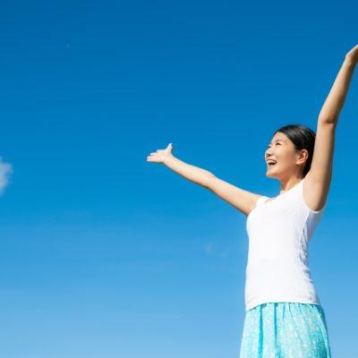 大空に両手を上げる女性